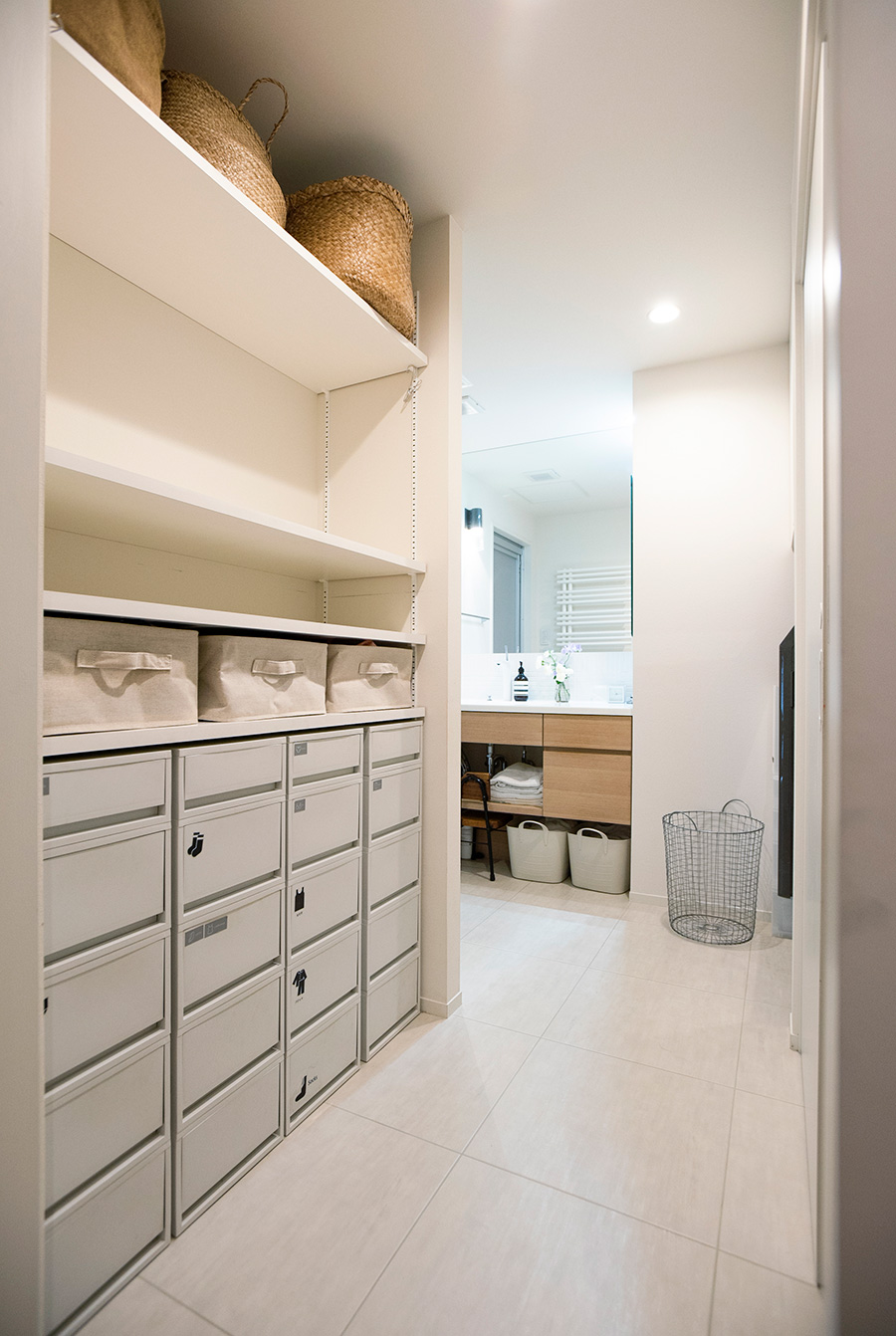 洗面所の入り口。右手にトイレ、ランドリー、左奥にバスルームがある。左手前の棚は、脱衣を仮置きできるようスペースを空けている。