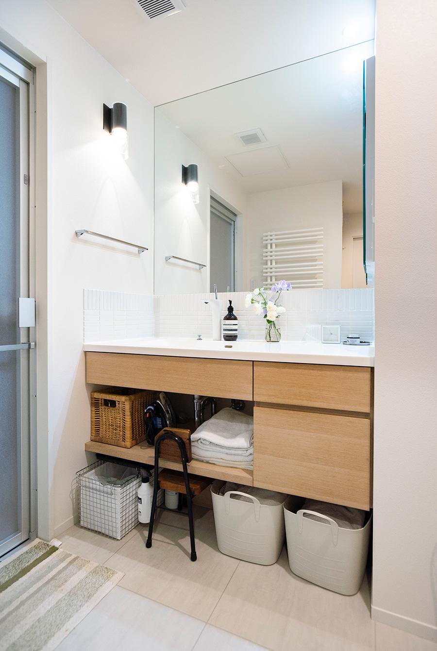 洗面台は、オークの突板にホワイトふき取り塗装をかけた素材で造作。下はオープンにして脱衣カゴなどを置くスペースに。