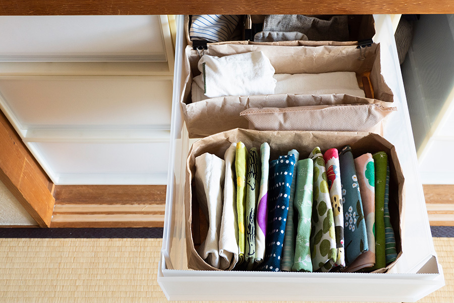 ショップの紙袋を収納ボックスに。手提げ部分をはずして外側に何回か折り曲げて使用。間には調湿の木炭を。