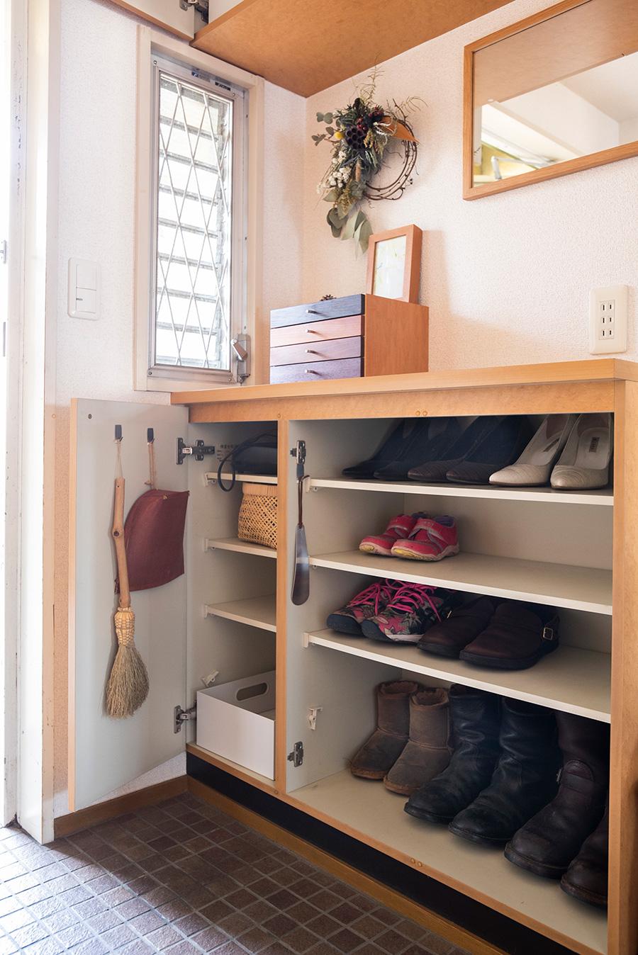 下駄箱の扉も外してオープンに。いちいち開けて靴を取り出す手間がなくなり、ストレスが激減したそう。玄関まわりで使う掃除道具はここにスタンバイさせている。