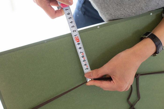 フレームをひっくり返し、裏面のヒモを引き上げた状態から、フレームの上部までの長さを測る。