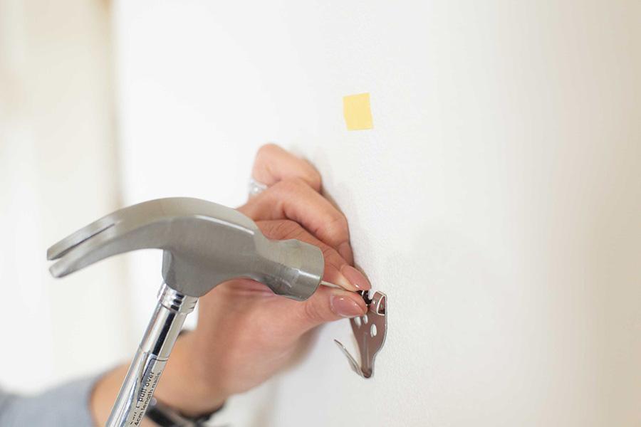 ピンを壁に打って固定する。「作品がとても軽い場合は、押しピン(画鋲)を使うこともあります」