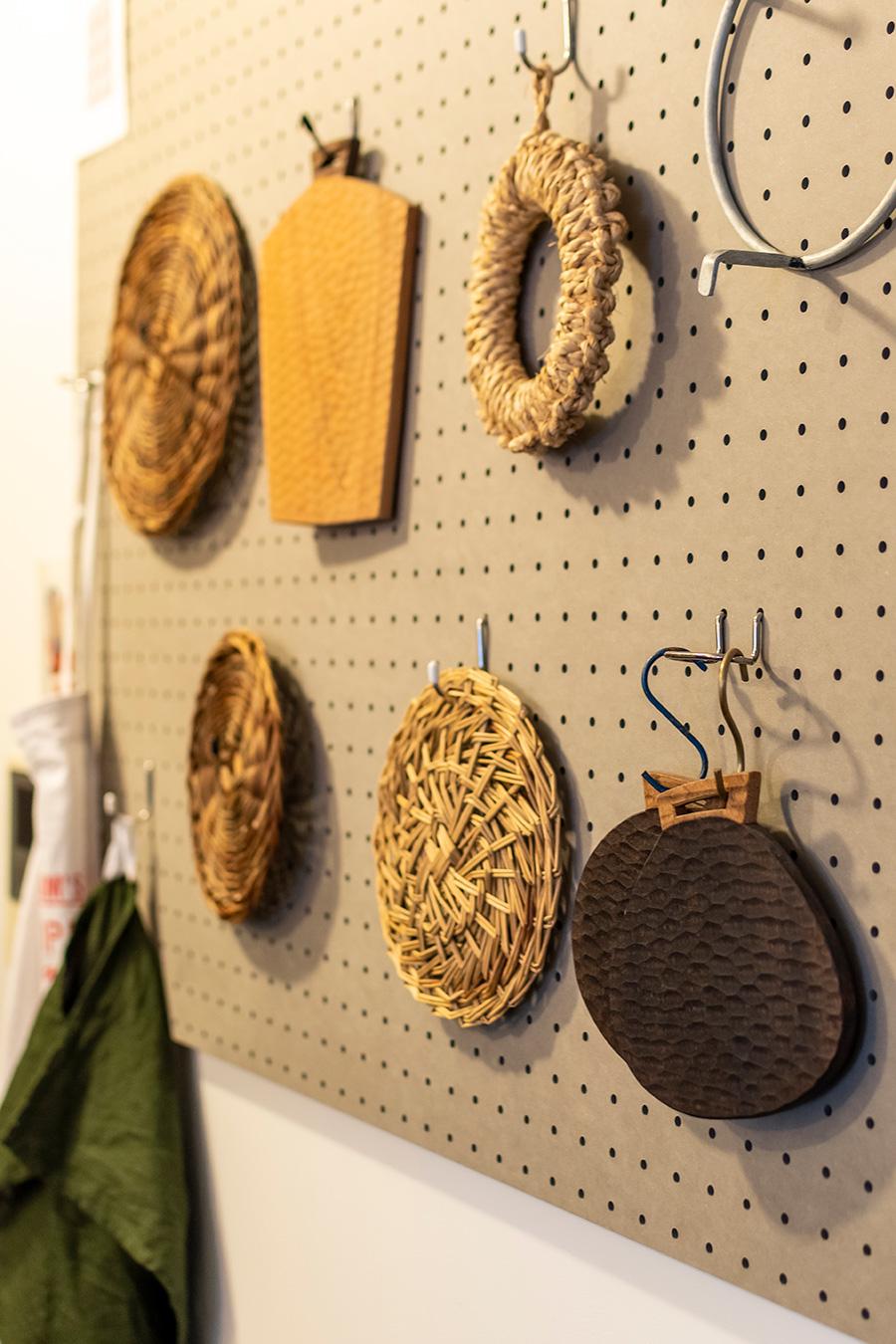 有孔ボードに「KOHORO」の鍋敷などを飾って。