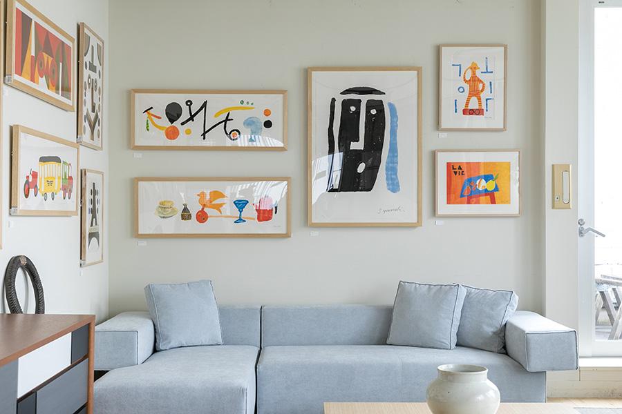 壁は白いキャンバス。壁全体を埋めるのではなく、フレームの縁を格子に見立てて組んでみるとよい。作品は、常設されている柚木沙弥郎のリトグラフ。