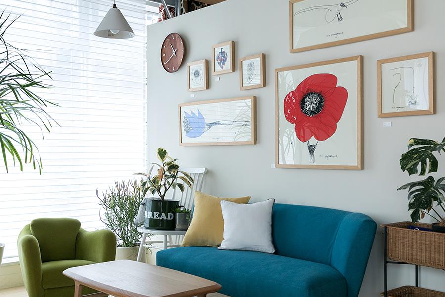 大きさ、形など様々なフレームを飾る。ソファーの色とのバランスで、色彩を加えるのも効果的。赤い花のポスターは、山口一郎の『HANA Red no.1』。