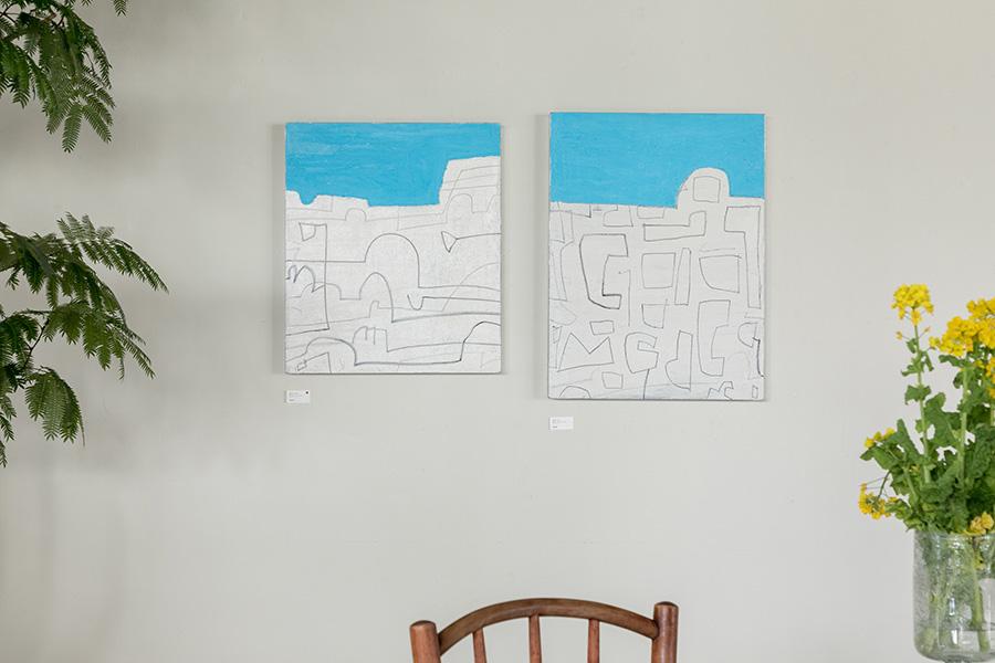 松林誠の『自由ケ丘Ⅰ』(右)と『自由ケ丘Ⅱ』(左)。街と空のラインを揃えて飾ることで、街並みが横に広がっていくことをイメージさせる。