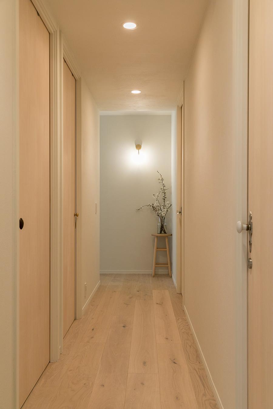 ベージュトーンの廊下の先に、季節の花を飾るコーナーを設けた。それぞれの扉に違うドアノブをつけ、物語を感じさせる廊下に。