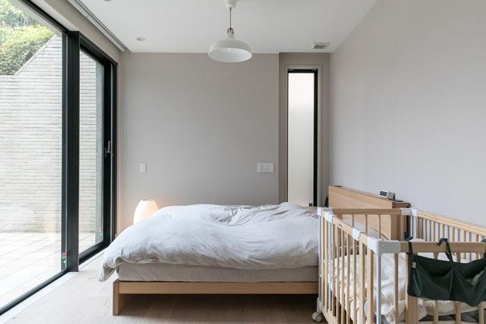 テラスに面した明るいベッドルーム。手前のベビーベッドは、子どもの成長に合わせて形を変えることができるタイプ。将来は学習机にもなるそう。寝室の壁は既存の壁紙を生かしながら、無相創オリジナルの樹脂左官に4000色の中から選んだ塗料を調合し、特殊左官と塗装で仕上げている。