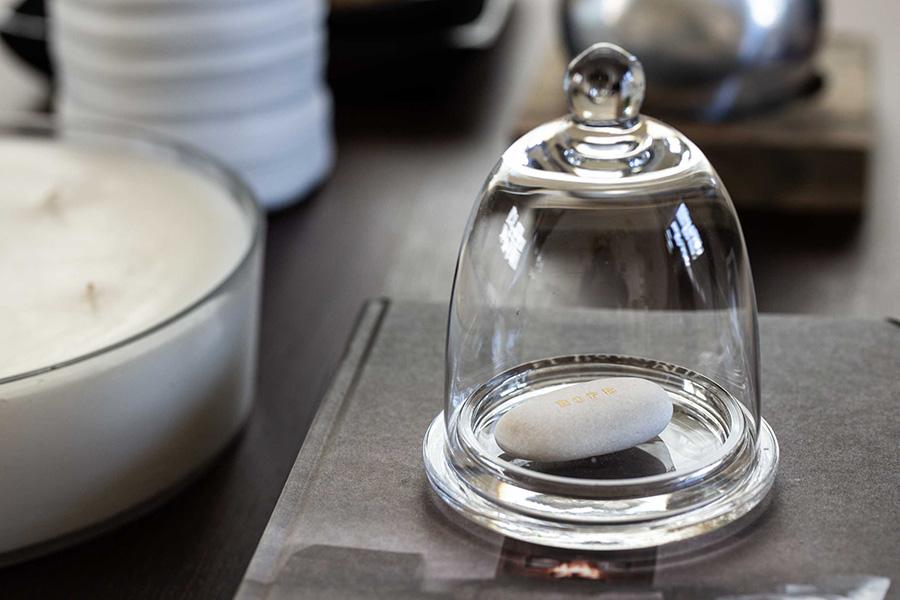 「HOPE」の文字が印象的な作品をガラスドームに閉じ込めて、リビングのテーブルの本やキャンドルと一緒に飾る。Artist:野田万里子