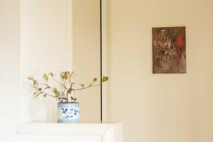 廊下のちょっとしたコーナーを生かして、立体的にアートを楽しむ。壁に作品を飾り、手前に野山の活け込みを。Artist:三瓶玲奈