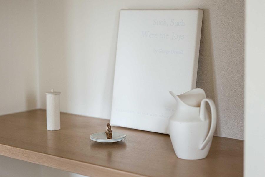 小さな仏像を中心に、白を基調とする作品でまとめた静謐な空間。Artist:平面はサイモン・モーレイ、仏像と経筒は二見光宇馬、ピッチャーは青木良太