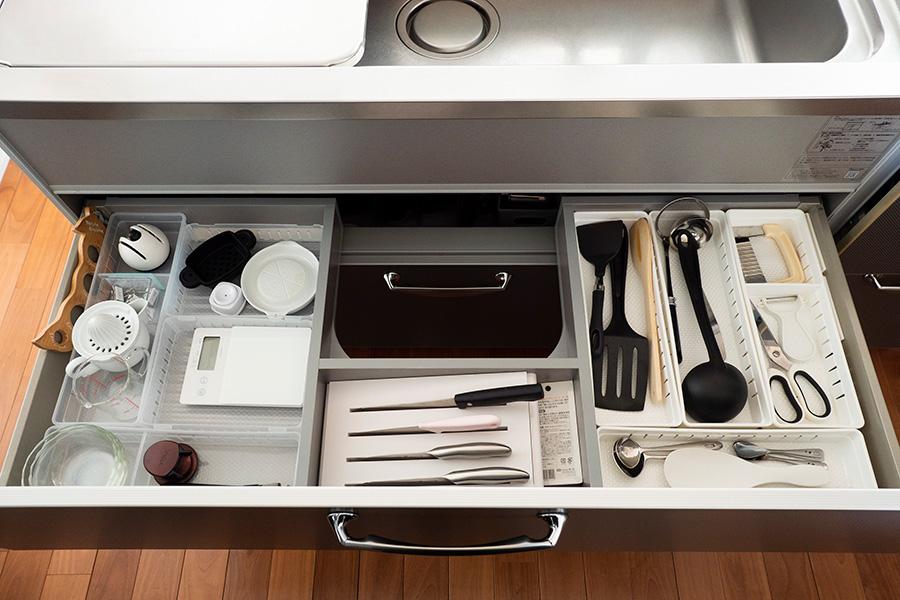 シンク下は、ぴったり収まるプラスチックケースを使い、調理器具を収納。