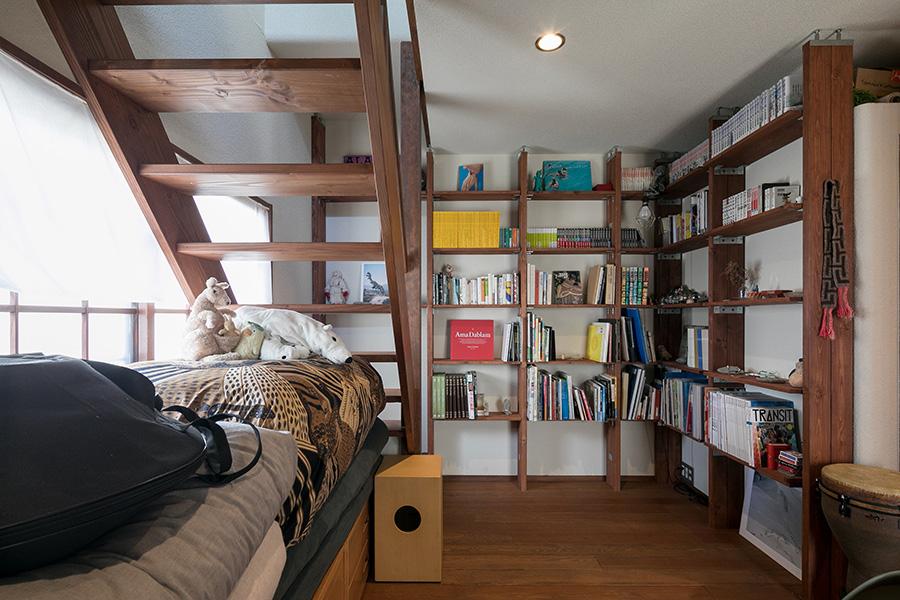 手づくりの壁一面の本棚。図書室のような篭れる雰囲気。光を通す、梯子のような階段で2階へ。
