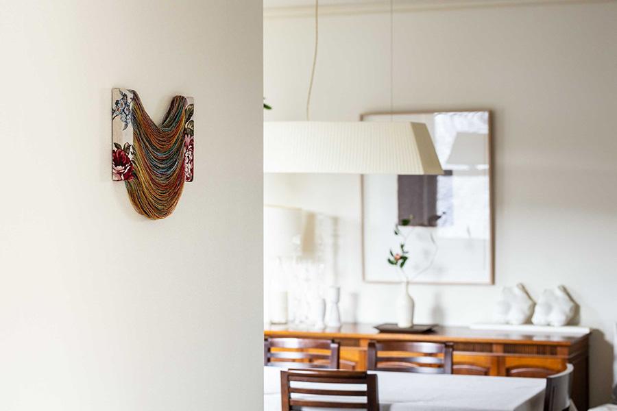 手前の立体的な作品と、奥のダイニングに飾った作品とが同時に目に入る。織物をほどくことで生み出されたコンセプチュアルな立体感のあるアート。手前左の作品:手塚愛子、奥のキャビネットの上のトルソー:大西伸明、壁にかけた作品:岩村伸一