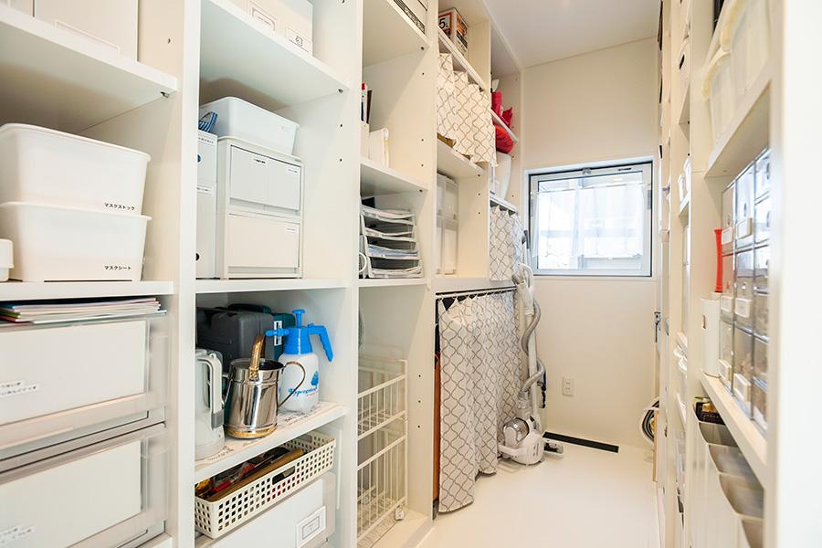 玄関とリビング側の2カ所から入れるウォークインシューズクローゼット。靴は、玄関の靴箱にすべて収納できる数に減らしたので、ここは靴のないシューズクローゼットに。外出時使うマスクや屋外で使うグッズ、取説など頻繁に使わないものも収納。