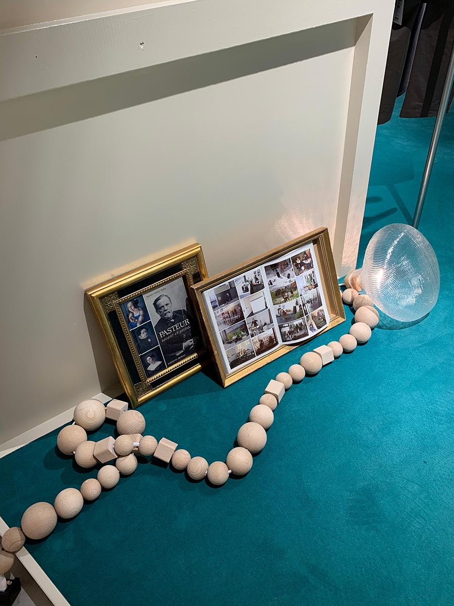 ブルーのカーペットに、無垢の木を使ったユニークなフォルムの延長コードや照明、ゴールドのフレームを床面にさりげなく置くアイディア。