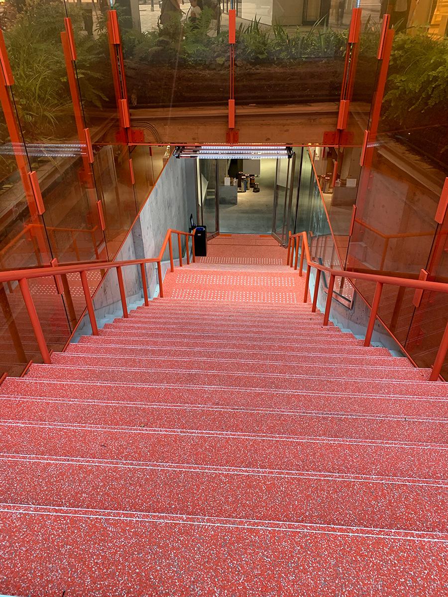 スキーマ建築計画によるオレンジ色のガラスで囲われた地下へ降りていく階段が印象的。