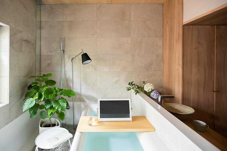 ハーフユニットを使った開放感たっぷりのバスルーム。手前にシャワーブースがあり、体を洗ってから入浴できる。