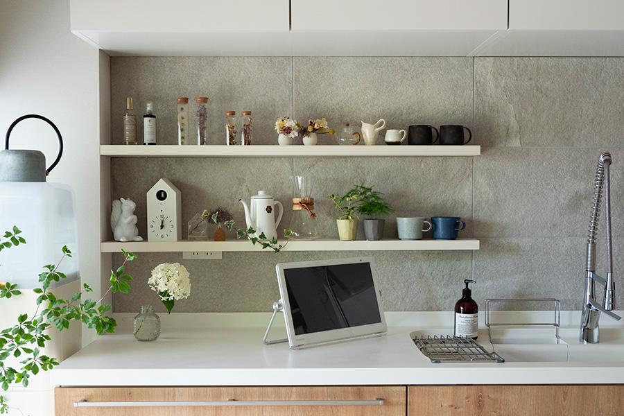 オープンシェルフを取り付けて飾り棚に。壁にはバスルームと同じタイルを使用した。