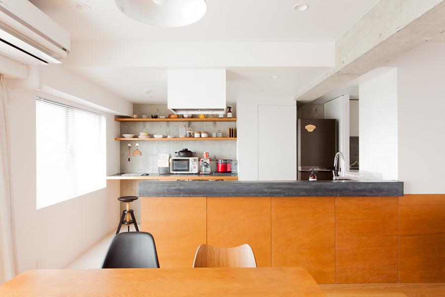 シンクやコンロはアイランドキッチン側に。ワークスペースは背面カウンターにコンパクトに。