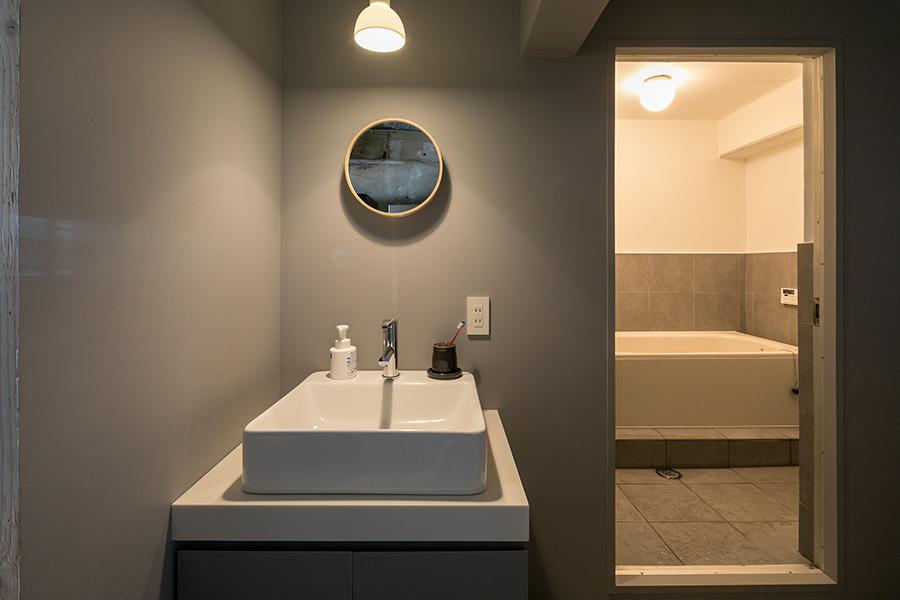 解体してみると予想外の場所に配管があり、苦労したバスルームと洗面所。壁のグレーは1階の『アキナイガーデン』と同じ色。