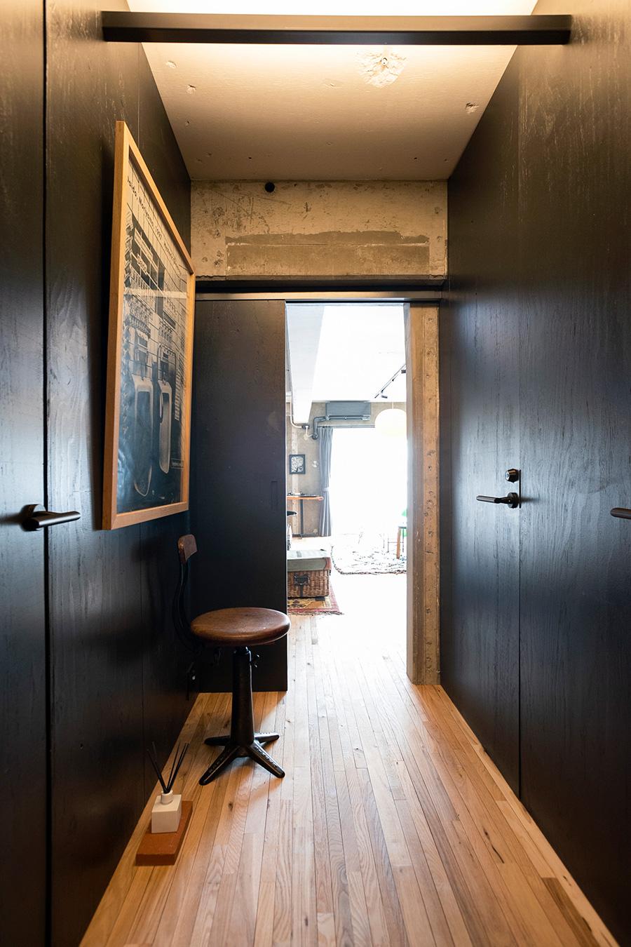 黒塀に包まれた廊下。細くシャープな床板がリビングまで続いている。構造壁をあえて出して個性的に。hysteric Daido vol.8のポスター下の1800年代シンガーミシンのイスは、イスにリクライニング機能をもたせた初期のもので、現在インダストリアル家具のアイコンのひとつになっている。