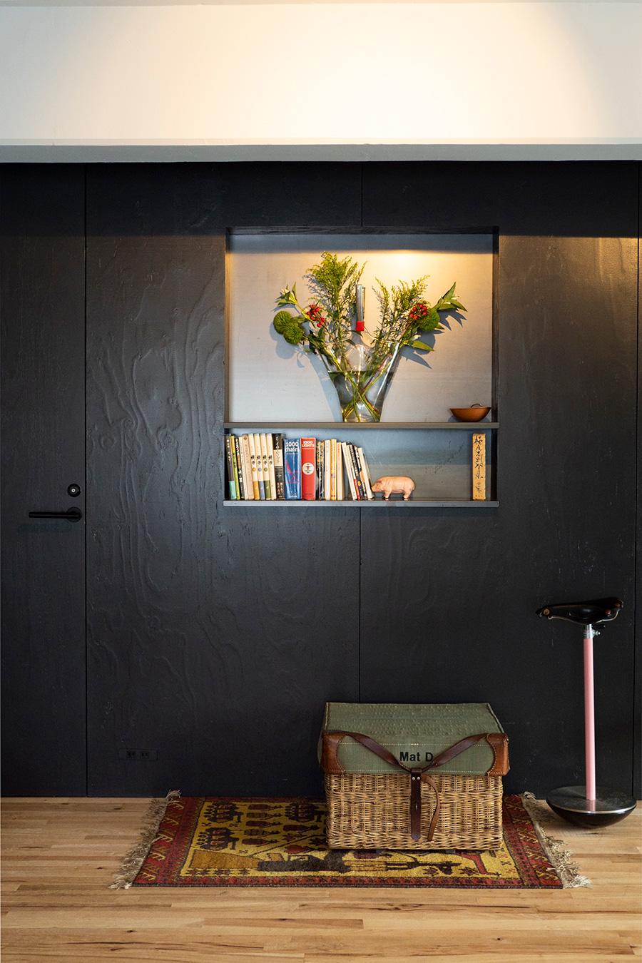 """うづくり模様が美しい壁のニッチに、和テイストの花をアレンジ。右手の""""ほとんど座れないイス""""は、ブルックス社のサドルを使ったザノッタのSELLA。「機能を無視しても成り立つプロダクトです」。"""