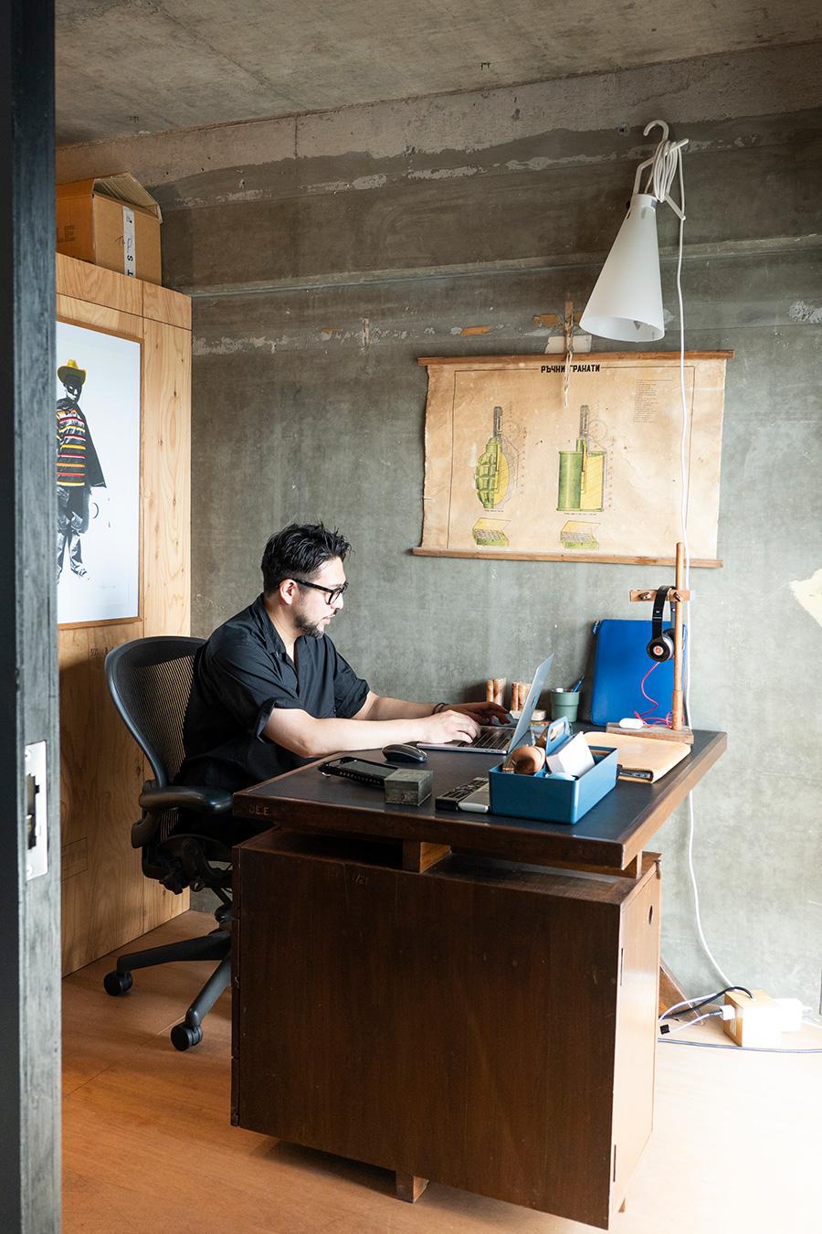 インドから来たピエール・ジャンヌレのPJ-030405 チークデスクで仕事をする古久保さん。