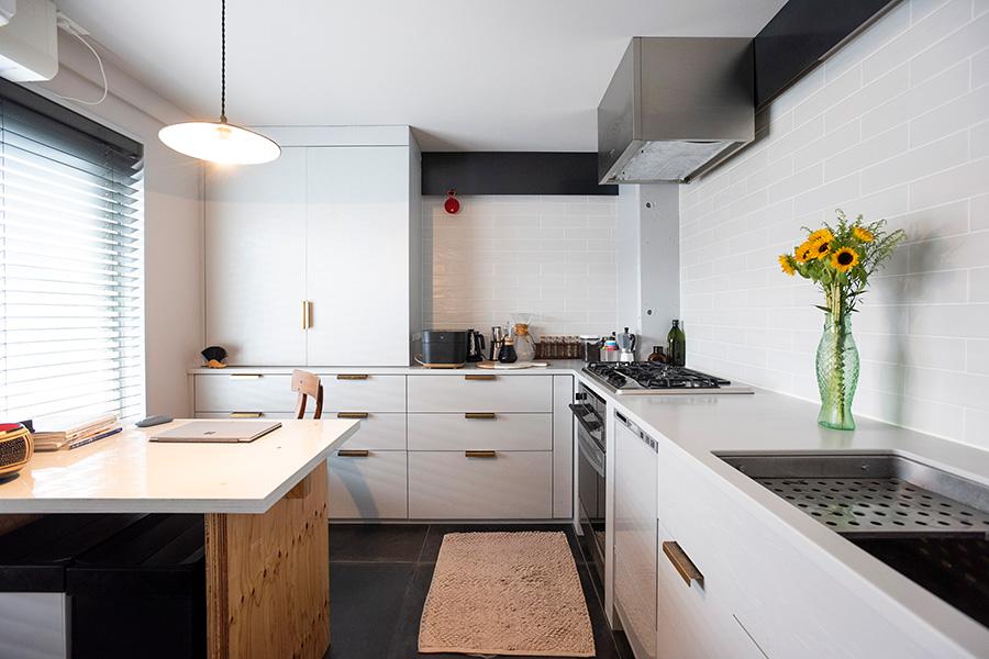 明るいモノトーンにした独立型のキッチン。キッチン台は収納を豊富に造作。水切りをシンクの内側に設定するなどをリクエストした。妻専用のテーブルはここに収まるサイズを考え、木の脚とウレタン塗装の天板で造作したもの。