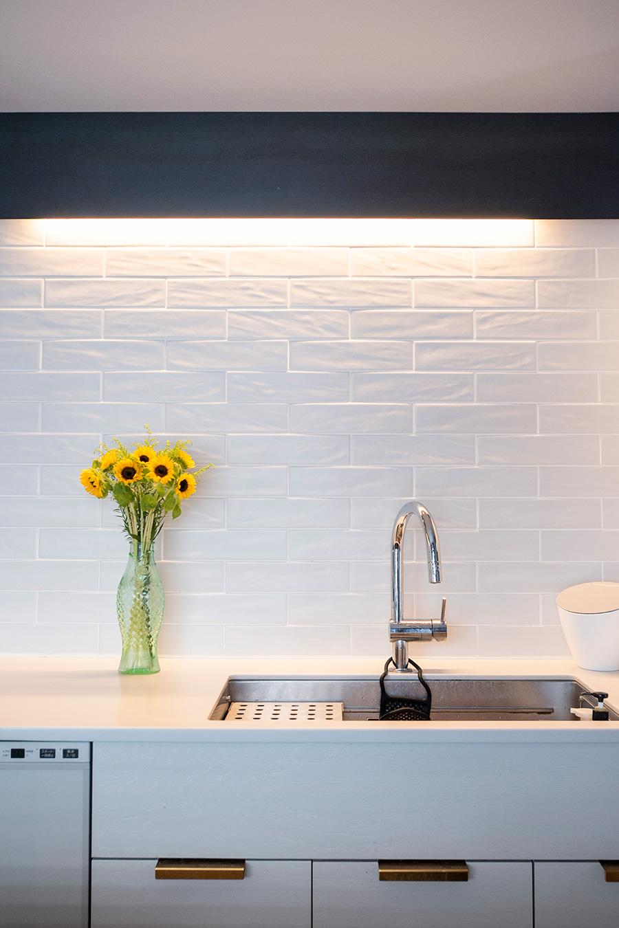 凹凸があり掃除がしやすいタイルをセレクト。鉄板の後側に間接照明をつけている。