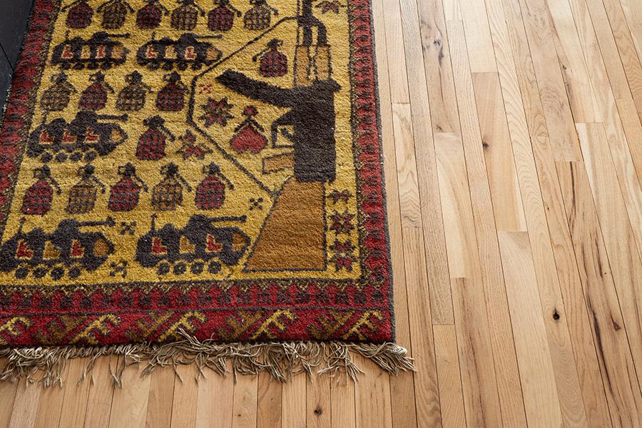 手織りのラグは、アフガニスタンの民藝品ウォーラグ。戦車などがモチーフで、戦争批判の意味が込められている。