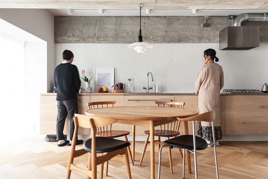 スケール感のあるキッチンに立つIさんご夫妻。ふたりで作業をしても余裕の広さ。