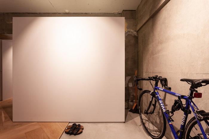 玄関のドアを開けると正面に間仕切り壁が現れる。左右から収納兼シューズクローゼットを通り抜け可能。