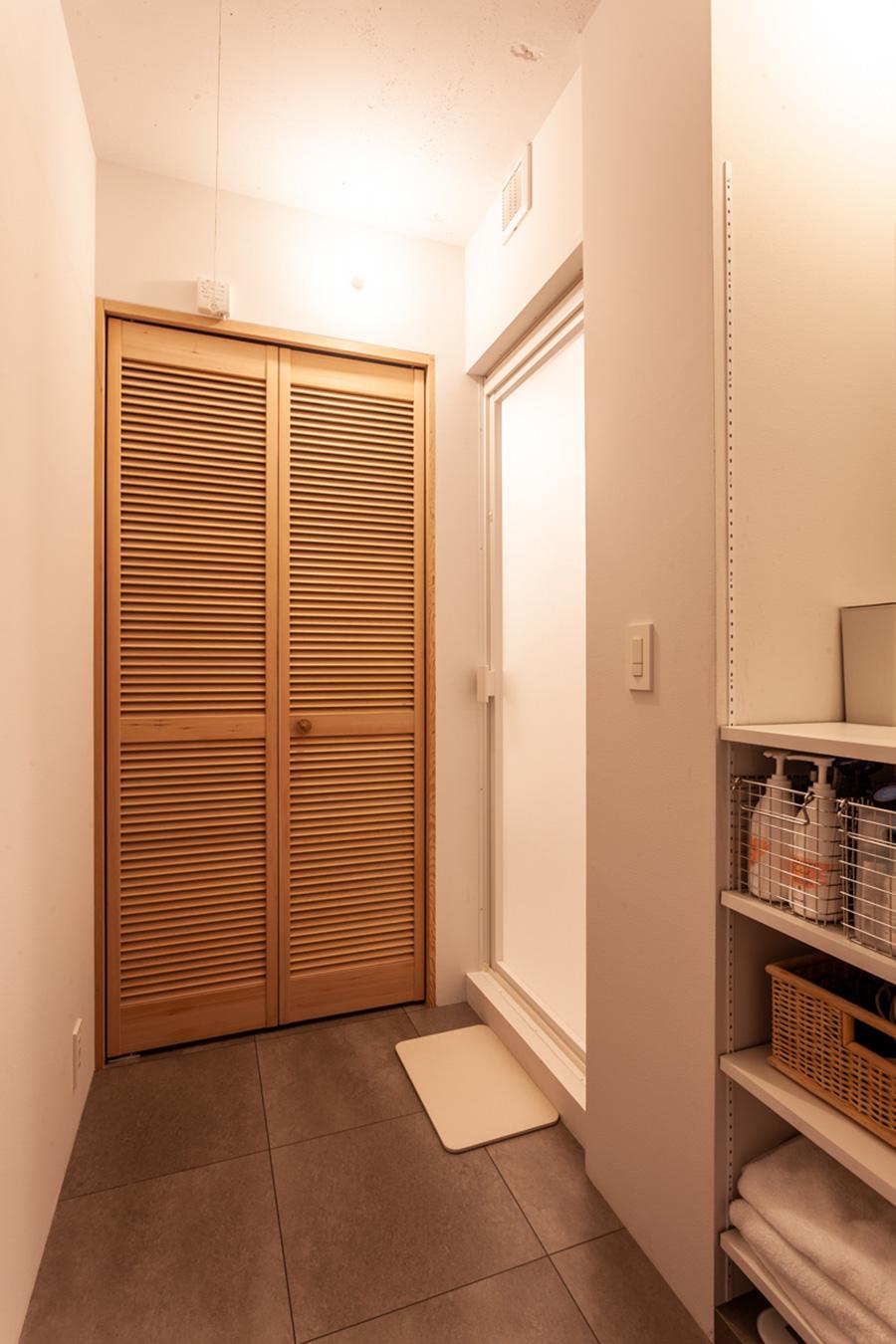 ドアの奥にある脱衣室とバスルーム。使うときだけ引き出せる洗濯ロープを設置。床にはグレーのタイルを。