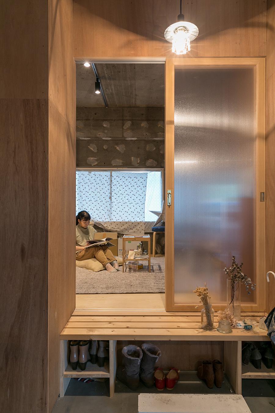 鶴田さんの部屋。縁側のような段差を上がり部屋に入る。靴はそれぞれの個室の入口で収納管理する。1段高くなっている居室の床下は物入れになっている。