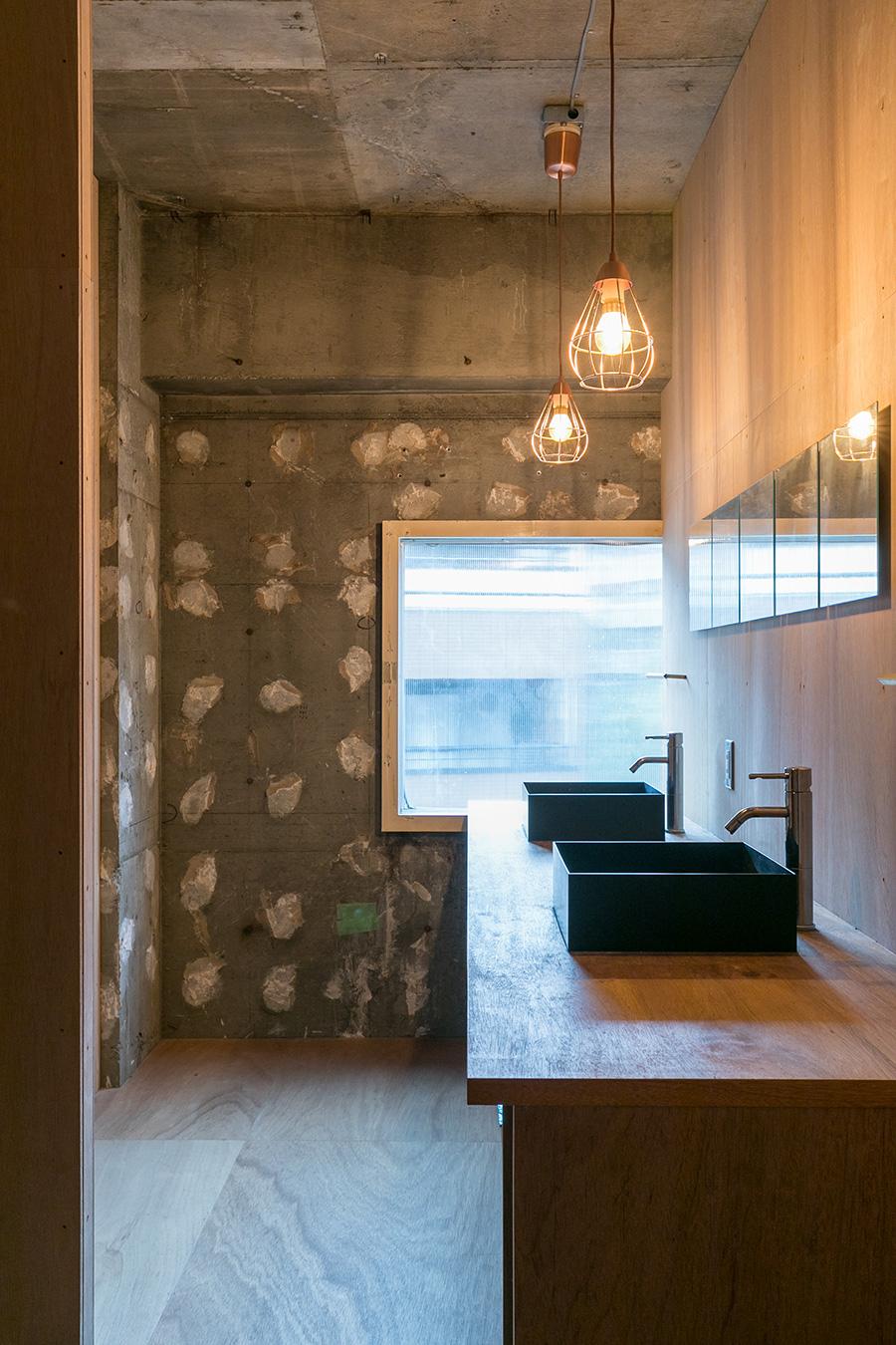 黒のスクエアなボウルがスタイリッシュな洗面スペース。鏡はIKEAで。他に、トイレが2つ、シャワー室が2つ、洗濯機が2台ある。