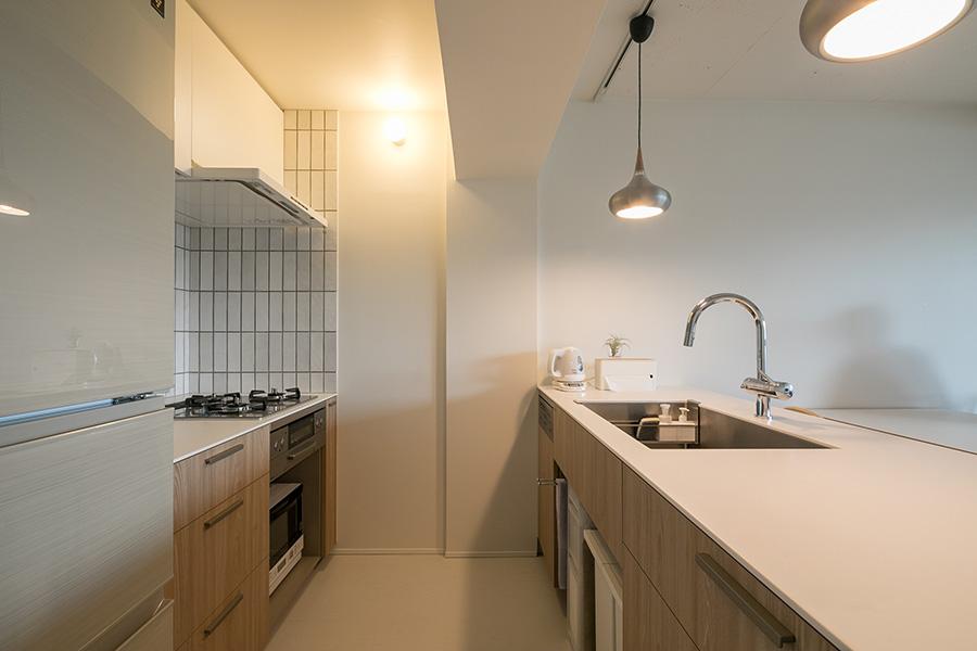 オープンなⅡ型キッチン。使いやすさを考慮し、コンロ側は五徳の高さの分、シンク側よりも低く設計している。