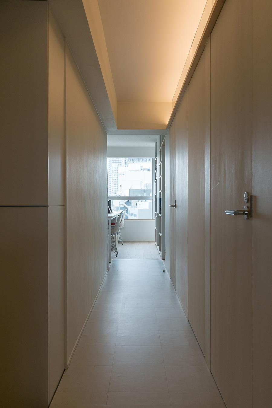 玄関から左手を向くと事務所スペース。廊下はあえて間接照明のみを使い、落ち着いた明るさに。