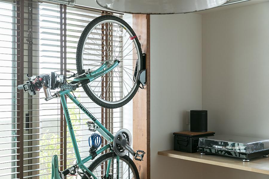 足場板を壁に設置し、自転車を掛けられるようにした。梁のように見え、ウッディな空間に自然と馴染む。