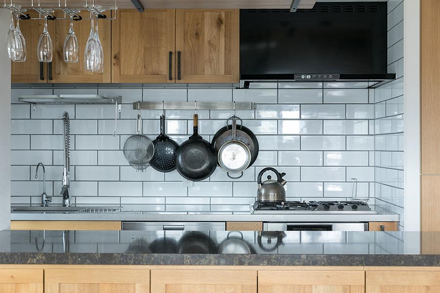 左利きの阪口さんに合わせ、コンロとシンクの位置を逆にした。オークの面材を使ったキッチンは天然素材を使用するインパクト社。