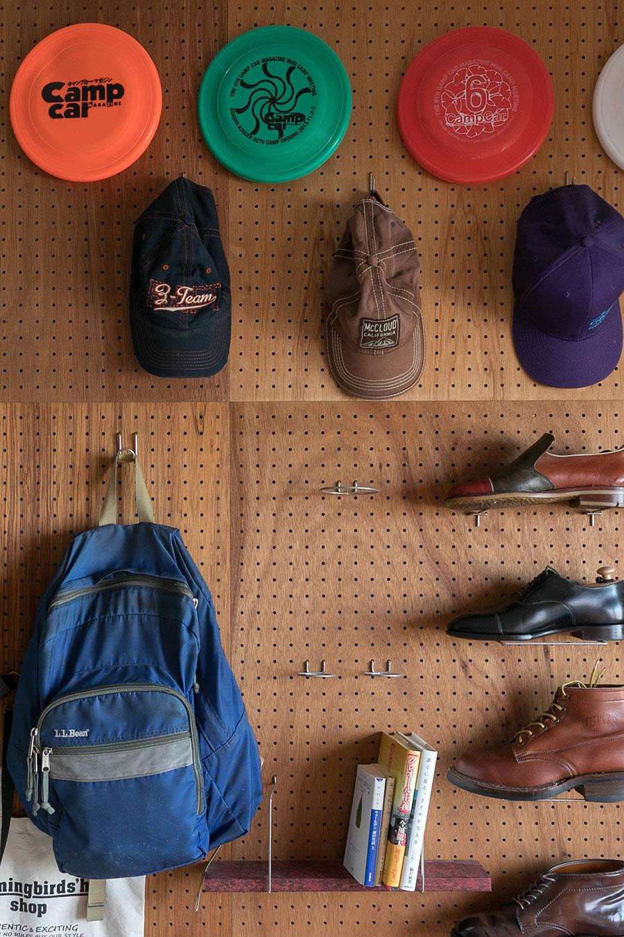 Tさんの部屋の壁には、有孔ボードを設け見せる収納にした。旅先で購入した帽子などが飾られている。