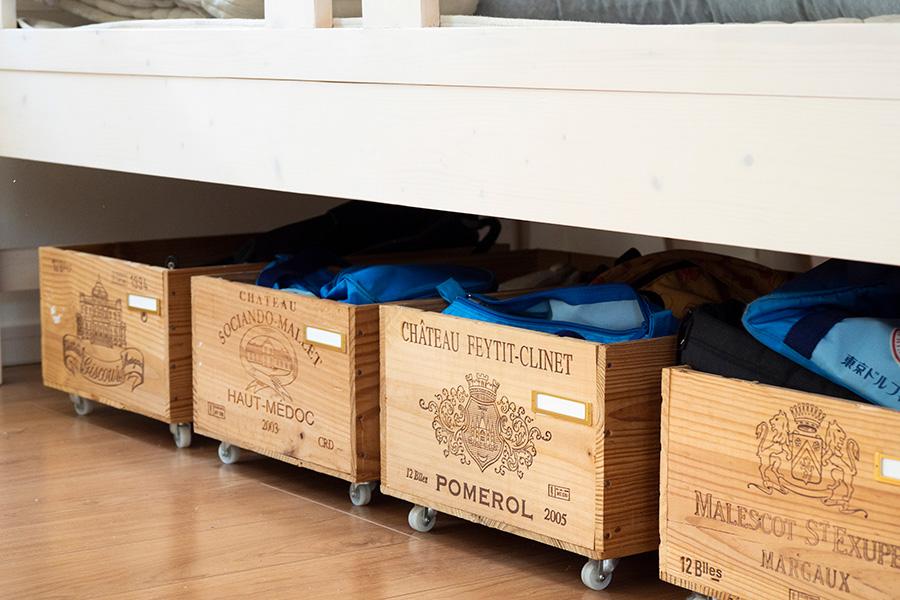 ワインケースにキャスターを付けて収納に。引出しやすく、ベッド下もうまく活用できる。