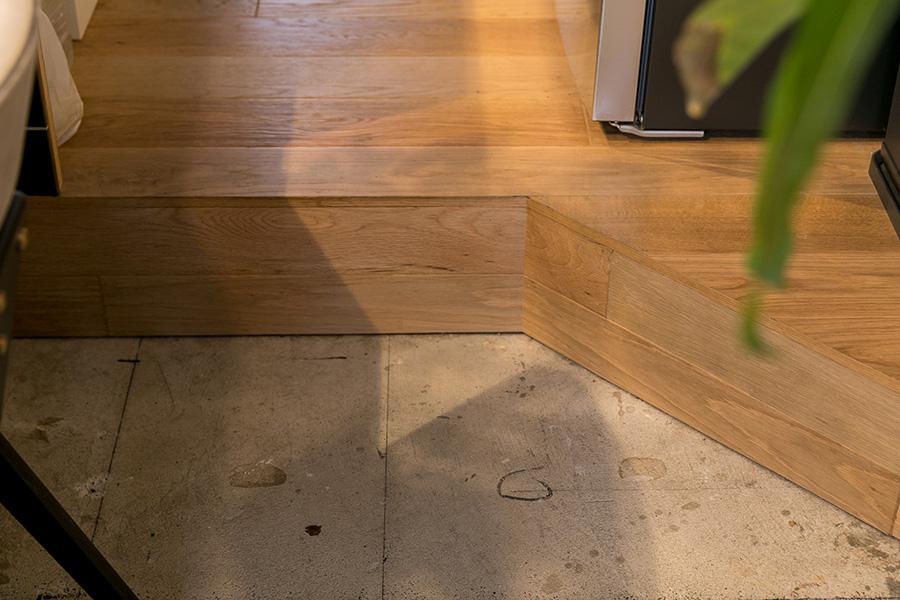 ダイニングとリビングはコンクリート現し、キッチンを一段高いフローリングにした。「フローリングは自分たちで貼りました。この三角の部分を作るのが大変でした」