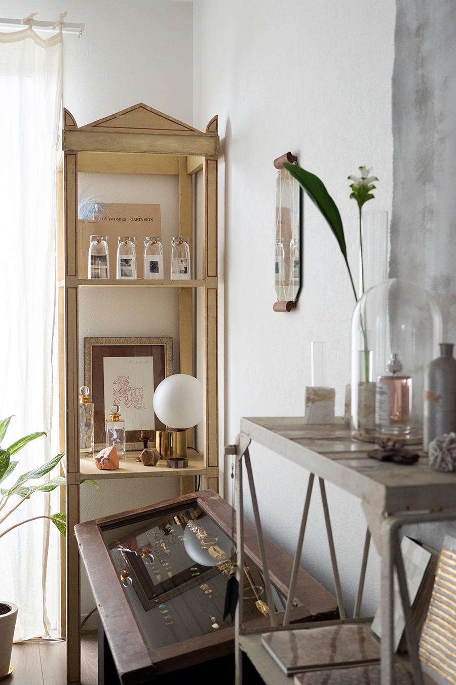 鉱石、ジュエリー、アンティークの雑貨など、お気に入りの雑貨を愛でるように飾ったコーナー。手前のシェルフの上には、ガラスドームに香水瓶をディスプレイ。壁にかけた鏡は古いトレー。