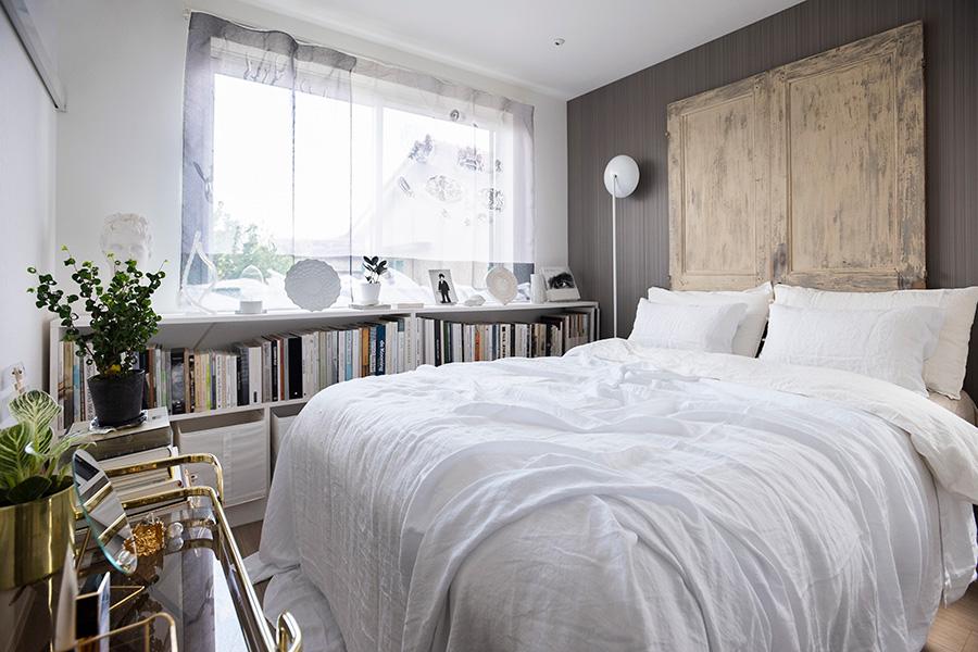LDKに対して色を抑えたベッドルーム。フランスの古い扉をヘッドボードに見立て、それに合わせてベッドを購入した。