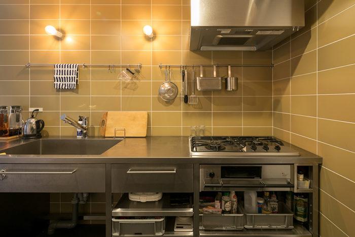 『平田タイル』のマスタードカラーのタイルと、『北沢産業』の業務用の造作ステンレスキッチン。収納にはグレーの無骨な業務用コンテナを使用。