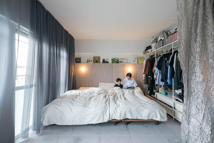 ベッドのヘッドボードの上に並んだ絵本を選んで読み聞かせ。リビングと寝室は『ファブリックスケープ』のカーテンでゆるやかに仕切る。窓際のカーテンはドレープを寄せれば明るさを調節できる。