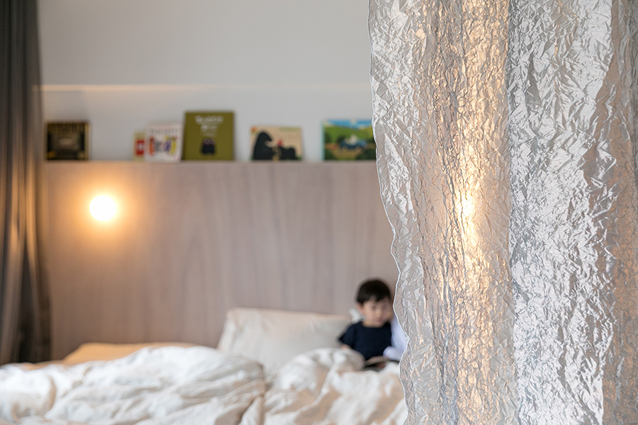 リビングと寝室をゆるやかに分ける、モダンな素材感のカーテン。
