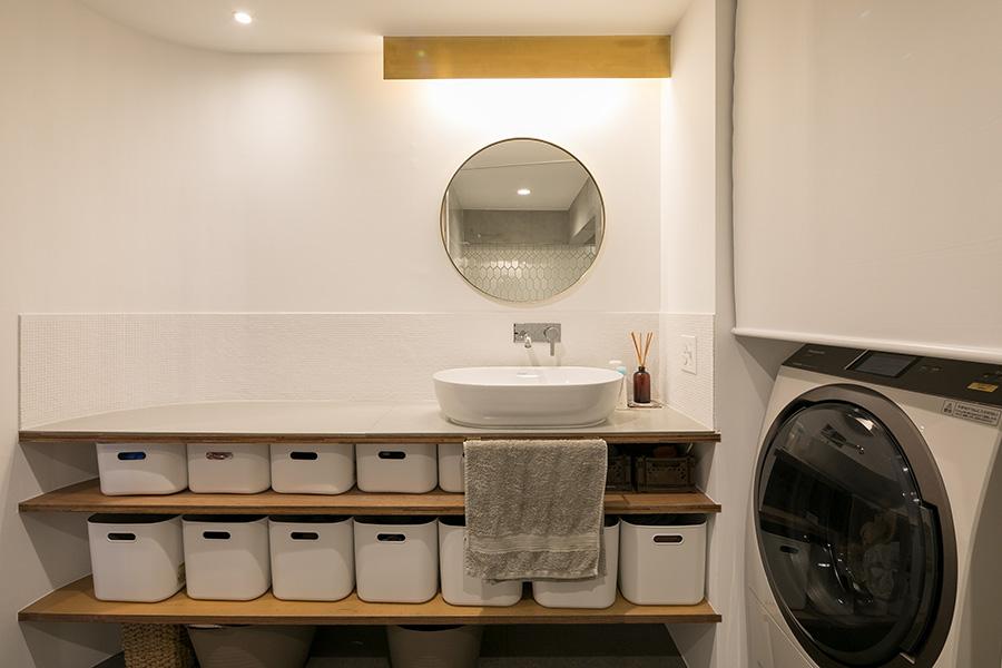 洗面所の小さな大理石を使った壁面のタイルは、曲線に沿って美しく仕上がっている。収納は無印良品のボックスに。「家族の下着類もここに入っています」。洗面ボウルは『デュラビット』。洗濯機はロールカーテンで隠すこともできる。