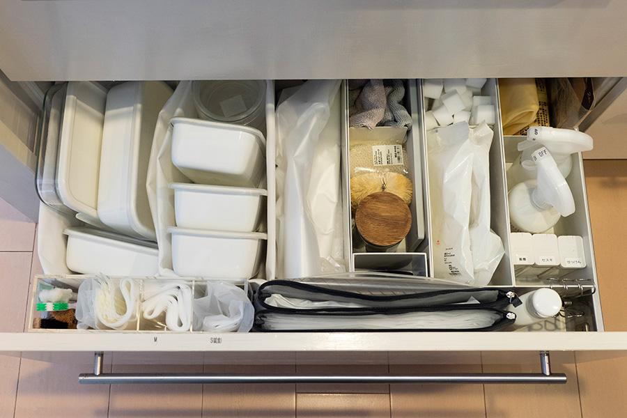 シンク下には衛生グッズやよく使う保存容器などを。長く使えて匂い移りもないため愛用している琺瑯やガラスの容器は、蓋を外さず一緒に収納。場所を取ってもその方が使うときワンアクションで済む。